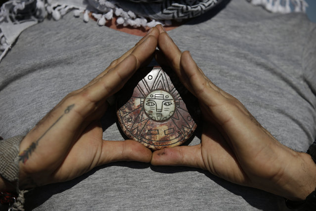 A Mexican man holds a talisman from Peru to his chest as he takes in the sun while celebrating the spring equinox atop the Pyramid of the Sun, at the Teotihuacan archeological site in Mexico, Tuesday, March 21, 2017. Although the official vernal equinox occurred on Monday, thousands of visitors were expected to climb the ancient pyramid between Sunday and Tuesday to greet the sun and celebrate the beginning of spring. (Photo by Rebecca Blackwell/AP Photo)
