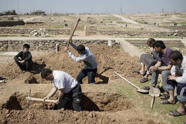 Relatives and friends dig the graves of two civilians killed during fighting between Iraqi security forces and Islamic State militants on the western side of Mosul, Iraq, Saturday, March 25, 2017. (Photo by Felipe Dana/AP Photo)