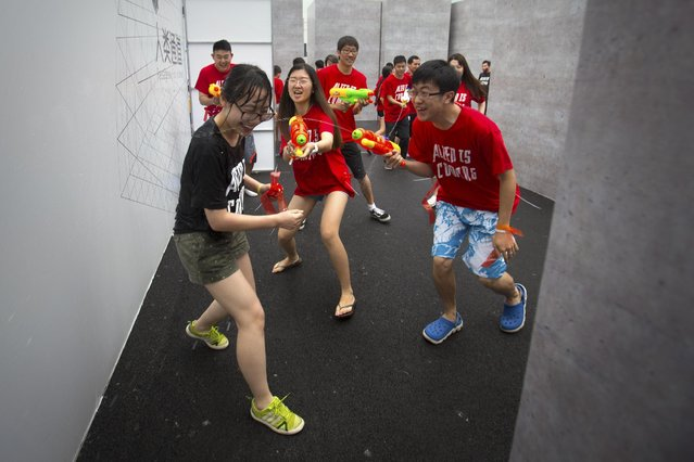 Players fire their water guns in a battle maze in Beijing, Saturday, July 4, 2015. (Photo by Mark Schiefelbein/AP Photo)