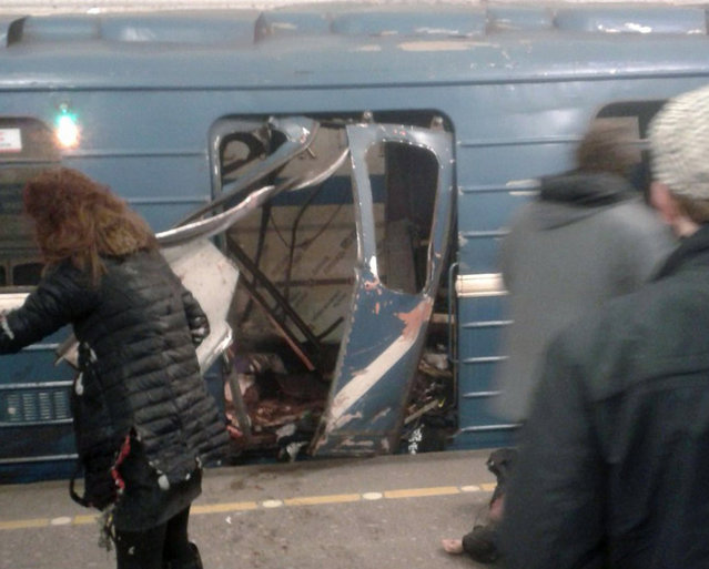 A handout photo made available by megapolisonline.ru via VKontakte (VK) shows people in front of a damaged train door shortly after an explosion in a metro of Saint Petersburg, Russia, 03 April 2017. According to reports, at least 10 people were killed and dozens injured in an explosion in the city's metro system. The cause of the blast was not immediately known. Russia's National Anti-Terrorist Committee said that the explosions hit a train between Sennaya Ploshchad and Tekhnologichesky Institut stations, media added. An anti-terror investigation is underway. (Photo by EPA/Megapolisonline.ru)