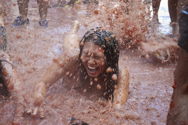 People participate in a Tomato Fight during La Tomatina Festival on August 28, 2019 in Bunol, Spain. The Tomatina Festival began in 1945 but was forbidden during the Franco Regime, in 2018 around 65% of the 22,000 revelers were foreign throwing around 150 tonnes of ripe tomatoes . Two rules state only tomatoes may be thrown and that they must be squashed before launch. (Photo by Borja B. Hojas/Getty Images)