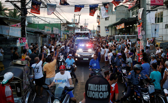 Supporters cheer as a motorcade of Presidential candidate Jejomar Binay and Filipino boxer and Senatorial candidate Manny Pacquiao, passes by during election campaigning in Malabon Metro Manila in the Philippines May 6, 2016. (Photo by Erik De Castro/Reuters)