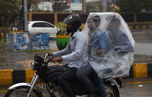 A Pakistani motorcyclist rides on a street as their passengers try to keep dry under plastic covering during monsoon rain in Karachi on July 29, 2019. (Photo by Asif Hassan/AFP Photo)