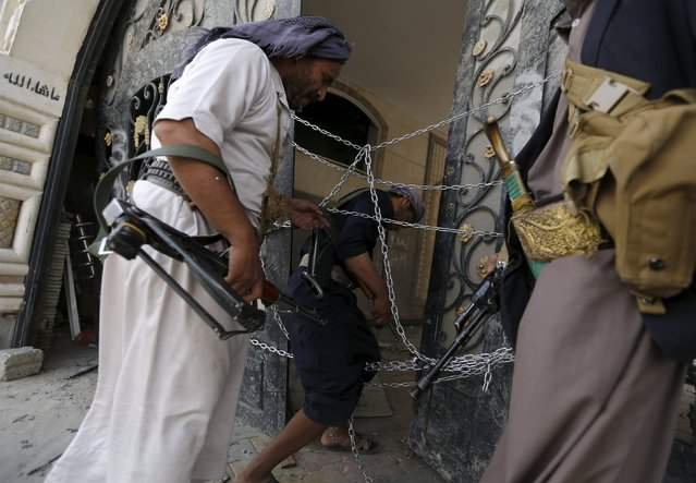 Guards walk through a damaged gate of the house of Brigadier Khaled al-Anduli, an army commander loyal to the Houthi movement, after it was hit by Saudi-led air strikes in Yemen's capital Sanaa July 6, 2015. Yemen's exiled government said on Monday it expects a deal shortly on a humanitarian ceasefire that would run through the Muslim Eid al-Fitr holiday later this month, as the capital Sanaa came under renewed air strikes. (Photo by Khaled Abdullah/Reuters)