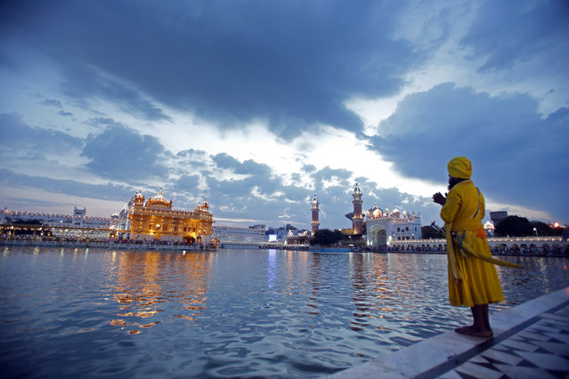 A baptized Sikh man prays in the pre-dawn hours as he visits to pay obeisance at the Golden Temple, the holiest of Sikh shrines, on the occasion of Visakhi festival in Amritsar, India, April 14, 2014. On Visakhi Day of 1699 A.D. Guru Gobind Singh ji, the tenth Sikh Master organized the Sikhs under one order called The 'Khalsa Panth'. The Visakhi festival also marks the beginning of the Sikh New Year. (Photo by Raminder Pal Singh/EPA)
