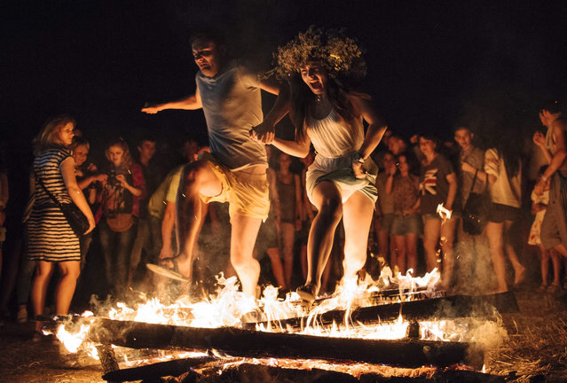 Ukrainians jump over a fire in Kiev, Ukraine, 06 July 2015, as they celebrate the traditional pagan holiday of Ivana Kupala, which is the Summer Solstice. Ivana Kupala is celebrated in Ukraine, Belarus, Poland and Russia on the night of 06 July. (Photo by Roman Pilipey/EPA)