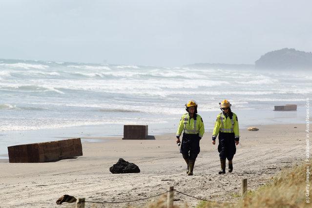 Firemen walk along Waihi Beach on January 9, 2012 in Tauranga, New Zealand