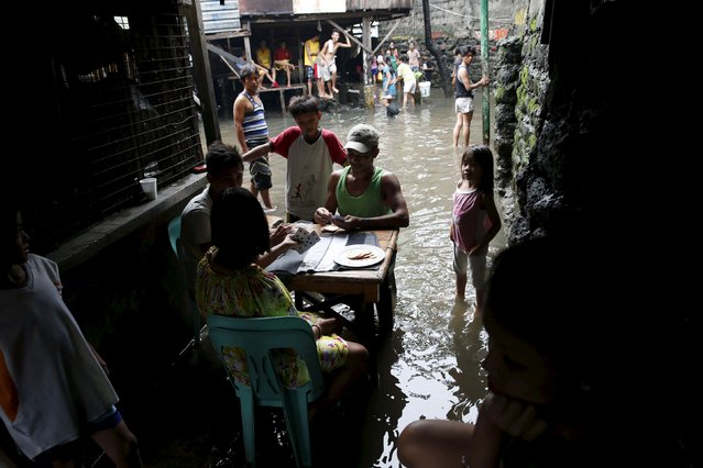 Residents play cards in knee-deep floodwaters at a squatter colony beside a creek in Malhacan, Meycauayan Bulacan north of Manila in the Philippines July 10, 2015. About 900 families were forcibly evacuated from their homes due to continous rain and flooding in nearby Bulacan province north of Manila on Friday, local government officials said. (Photo by Erik De Castro/Reuters)