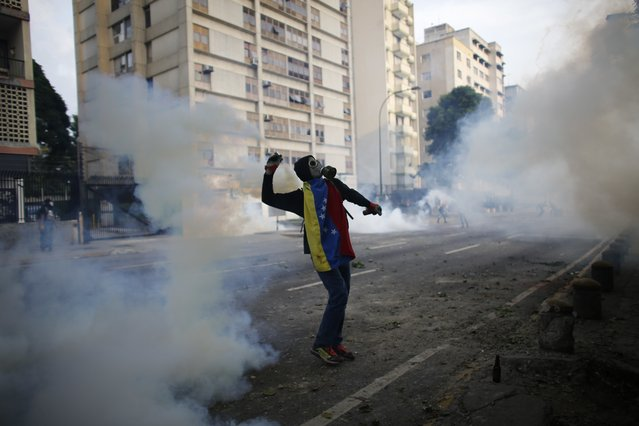 A demonstrator returns a canister of tear gas towards security forces during anti-government protests in Caracas, Venezuela, Wednesday, April 19, 2017. (Photo by Ariana Cubillos/AP Photo)