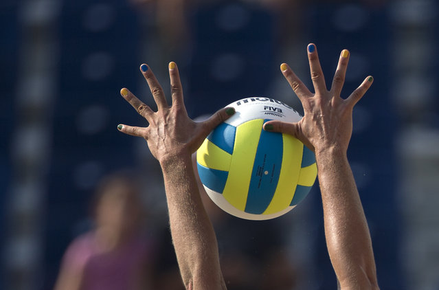 Brazil's Liliane Maestrini, with her fingernails painted in the colors of the national flag, blocks the ball, during Brazil's beach volleyball preliminary match against Nicaragua at the Pan Am Games in Toronto, Monday, July 13, 2015. (Photo by Rebecca Blackwell/AP Photo)