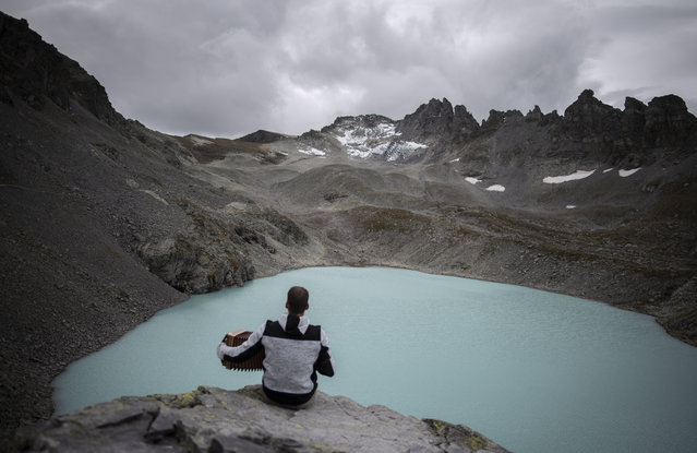 "A hiker plays his accordion with view of Wildlake and the Pizol glacier on the sideline of a commemoration for the ""dying"" glacier of Pizol mountain, pictured in the background, in Wangs, Switzerland, Sunday, September 22, 2019. Various organizations gathered to shine a light on climate change and melting glaciers. (Photo by Gian Ehrenzeller/Keystone via AP Photo)"