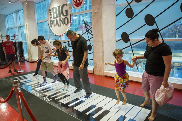 "Tourists play on the ""Big"" piano inside of the toy store FAO Schwarz on the last day that the store will be open in New York, July 15, 2015. FAO Schwarz will officially close the doors of its flagship Fifth Avenue toy store in New York City on Wednesday night, to the dismay of shoppers charmed by the iconic destination for childhood fun. (Photo by Lucas Jackson/Reuters)"