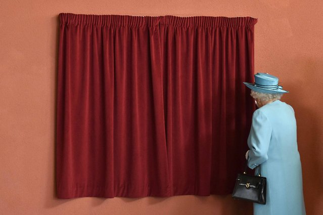 Britain's Queen Elizabeth prepares to unveil a plaque during a tour of Sydney Russell School in Dagenham, east London, July 16, 2015. The Queen and Prince Philip were visiting various parts of Barking and Dagenham as part of the celebrations to mark the fiftieth anniversary of the London Borough. (Photo by Toby Melville/Reuters)