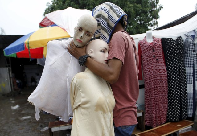 A worker carries mannequins past a clothing stall in a market in Jakarta, Indonesia February 4, 2016. (Photo by Garry Lotulung/Reuters)