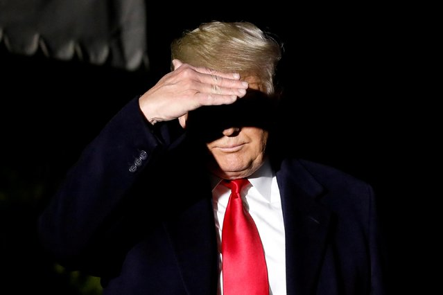 U.S. President Donald Trump covers his face from TV lights as he walks towards the media on the South Lawn of the White House in Washington, U.S., before his departure to New York, November 2, 2019. (Photo by Yuri Gripas/Reuters)