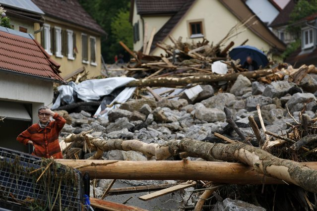 A woman reacts as she looks at the damage caused by the floods in the town of Braunsbach, Germany, May 30, 2016. (Photo by Kai Pfaffenbach/Reuters)