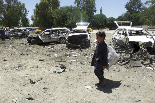 A boy walks passed damaged vehicles at the site of a suicide attack in eastern Khost province, Afghanistan, Saturday, May 27, 2017. At least 18 people, mostly civilians, were killed Saturday when a suicide car bomber targeted a convoy of provincial security forces in eastern Afghanistan, an Interior Ministry official said. (Photo by Nishanuddin Khan/AP Photos)