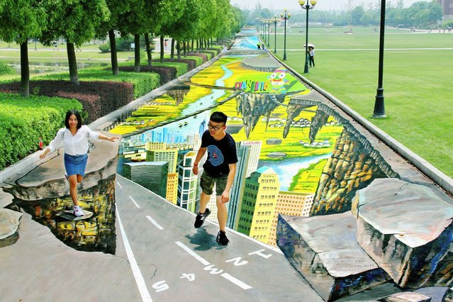 College students pose for pictures with a 3D painting along a street at a campus in Nanjing, Jiangsu province. (Photo by Reuters/China Daily)