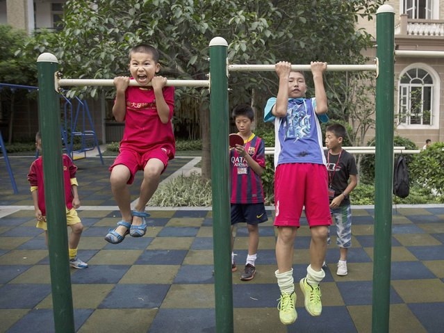 Children exercise on pull-up bars at the Evergrande International Football School on June 12, 2014 near Qingyuan in Guangdong Province. (Photo by Kevin Frayer/Getty Images)