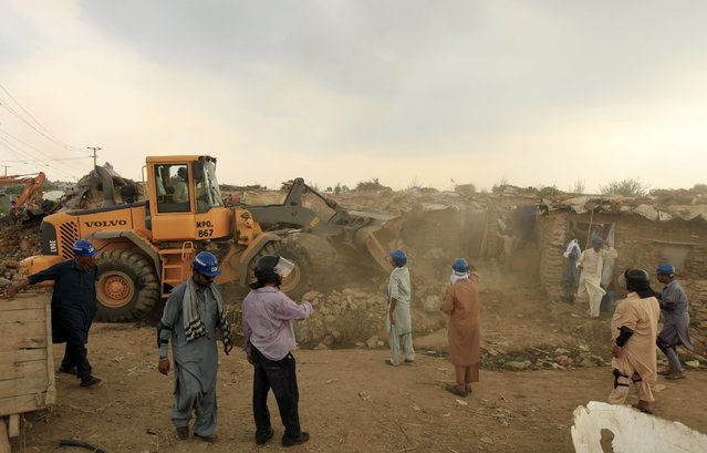 Officials use a bulldozer to demolish illegal houses at a slum on the outskirts of Islamabad July 30, 2015. (Photo by Faisal Mahmood/Reuters)