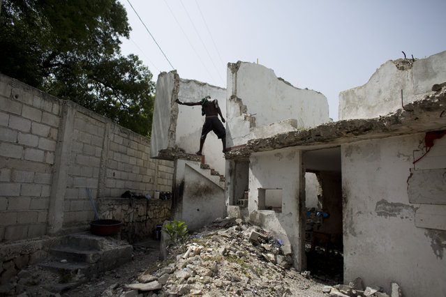 In this June 29, 2015 photo, a resident of the earthquake-damaged Hotel Le Palace makes his way downstairs from the room he inhabits in central Port-au-Prince, Haiti. Though much of the hotel was destroyed, some of the guest rooms, which still have intact walls, have become homes to people displaced by the quake. The ruined hotel has no running water or working sanitary facilities. (Photo by Rebecca Blackwell/AP Photo)