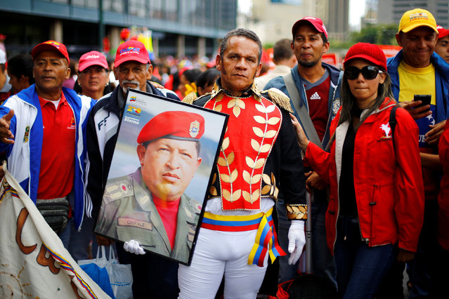 A man dressed as Venezuelan national independence hero Simon Bolivar, holds a picture of Venezuela's late President Hugo Chavez during a rally of members of the education sector in Caracas, Venezuela June 14, 2016. (Photo by Ivan Alvarado/Reuters)