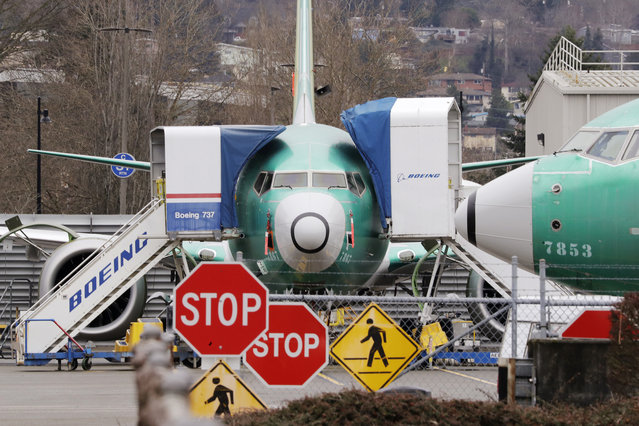 In this Monday, December 16, 2019, file photo, Boeing 737 Max jets sit parked in Renton, Wash. Newly released Boeing documents show that company employees knew about problems with flight simulators for the now-grounded 737 Max jetliner and talked about misleading regulators. (Photo by Elaine Thompson/AP Photo/File)