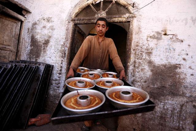 Afghan boy prepares traditional sweets ahead of the Muslim festival of Eid Al-Adha, in Herat, Afghanistan, 22 September 2015. (Photo by Jalil Rfezayee/EPA)
