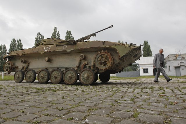 A man walks past an armoured personnel carrier ready for reconditioning at the 141th Zhytomyr Armor Mechanical Repair Plant in Zhytomyr July 10, 2014. Ukrainian forces regained more ground but sustained further casualties on Thursday in clashes with separatists, while two Western allies urged Russia's Vladimir Putin to exert more pressure on the rebels to find a negotiated end to the conflict. (Photo by Valentyn Ogirenko/Reuters)