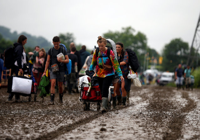 Revellers carry their belongings as they arrive at Worthy Farm in Somerset for the Glastonbury Festival, Britain June 22, 2016. (Photo by Stoyan Nenov/Reuters)