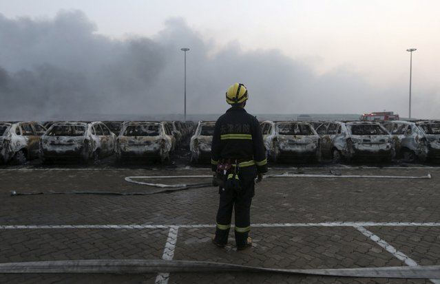 A firefighter looks on near damaged vehicles as smoke rises from the debris after the explosions at the Binhai new district in Tianjin, China, August 13, 2015. (Photo by Reuters/China Daily)