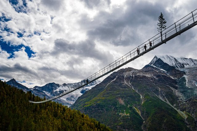 """People walk on the """"Europabruecke"""" bridge, the world's longest pedestrian suspension bridge with a length of 494m, after the official inauguration of the construction in Randa, Switzerland, 29 July 2017. The bridge is situated on the Europaweg that connects the villages of Zermatt and Graechen. (Photo by Valentin Flauraud/EPA)"""