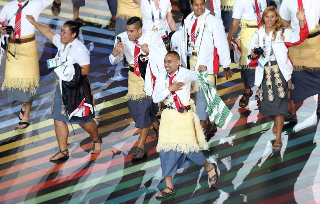 A Tongan athlete holds up a Celtic football team shirt as he takes part in the opening ceremony for the Commonwealth Games 2014 in Glasgow, Scotland, Wednesday July 23, 2014. (Photo by Scott Heppell/AP Photo)