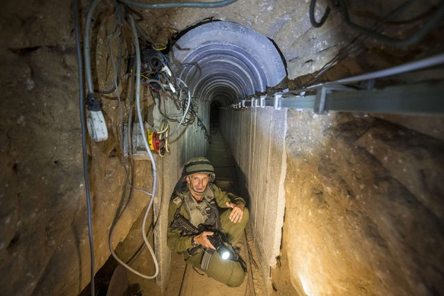 An Israeli army officer gives explanations to journalists during an army organised tour in a tunnel said to be used by Palestinian militants for cross-border attacks, July 25, 2014. U.S. Secretary of State John Kerry pressed regional leaders to nail down a Gaza ceasefire on Friday as the civilian death toll soared, and further violence flared between Israelis and Palestinians in the occupied West Bank and Jerusalem. (Photo by Jack Guez/Reuters)