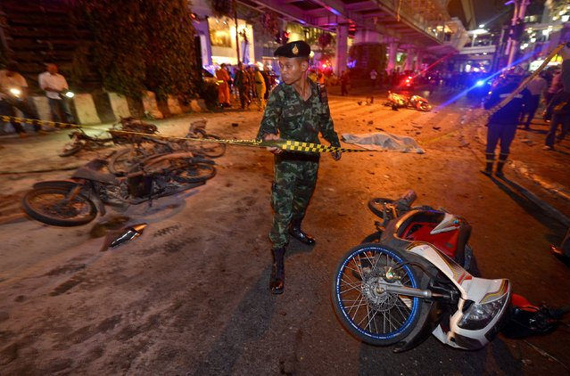 A Thai soldier ropes off the scene after a bomb exploded outside a religious shrine in central Bangkok late on August 17, 2015 killing at least 10 people and wounding scores more. (Photo by Pornchai Kittiwongsakul/AFP Photo)
