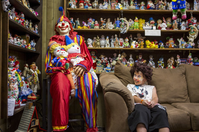 """Kai James, 9, glances over at the life-size clown known as """"Mr. Creepy"""" in the lobby of the Clown Motel in Tonopah on Tuesday, July 25, 2017. James came with his brother and mother from Las Vegas to stay for a night and dressed up in clown attire. (Photo by Patrick Connolly/Las Vegas Review-Journal via AP Photo)"""