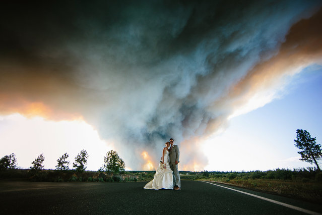 Wedding photographer, Josh Newton, has managed to turn a natural disaster into an amazing photo shoot opportunity. On June 7, 2014 Michael Wolber and April Hartley were getting ready to walk down the aisle in Rock Springs Ranch, Bend, Oregon, USA when firefighters alerted them to nearby wildfires gaining momentum and instructed them to flee to a safer location. (Photo by Josh Newton/IMP)