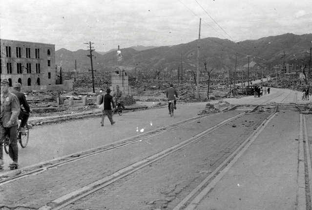 People walk past destroyed buildings at Aioi Bridge in Hiroshima, after the atomic bombing of Hiroshima, Japan, on August 6, 1945, in this handout photo taken by Shigeo Hayashi in October 1945 and released by the Hiroshima Peace Memorial Museum. (Photo by Shigeo Hayashi/Reuters/Hiroshima Peace Memorial Museum)