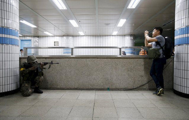 A South Korean soldier takes his position as a man takes photographs of him during an anti-terror drill in Seoul, South Korea, August 19, 2015. (Photo by Kim Hong-Ji/Reuters)