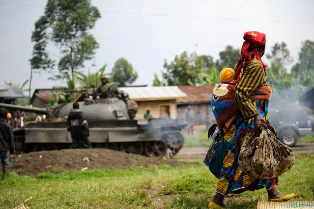 A displaced Congolese lady and her child walk past a retreating government army tank in the village of Rugari, around 37km from Goma, following an alleged ambush by M23 rebels in the Democratic Republic of the Congo's restive North Kivu province on July 26, 2012. This area has seen heavy fighting over the past three days, displacing thousands of people and increasing fears of a move by M23 on the provincial capital. Heavy fighting has continued today around Rumangabo, the headquarters of the Virunga National Park, just several kilometres from Rugari. (Photo by Phil Moore/AFP Photo)