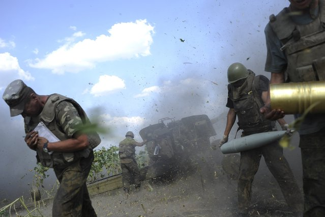 Ukrainian servicemen, who are members of an artillery section, take cover after firing a cannon during a military operation against pro-Russian separatists near Pervomaisk, Luhansk region August 2, 2014. (Photo by Maks Levin/Reuters)