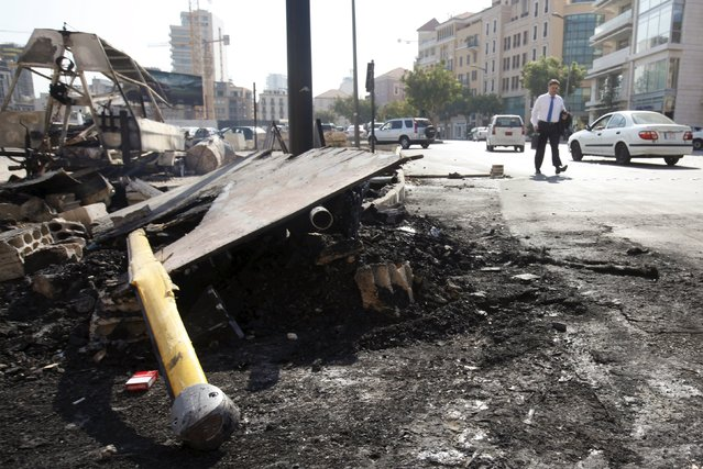 A man walks past a burnt police vehicle and charred remains of objects set on fire on Sunday by protesters in downtown Beirut, Lebanon August 24, 2015. (Photo by Jamal Saidi/Reuters)