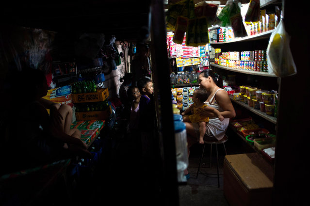 A mother holds her child as she tends to her makeshift grocery stall inside a cramped settler community on August 11, 2014 in Manila, Philippines. (Photo by Dondi Tawatao/Getty Images)