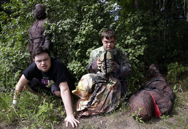 """In this July 12, 2016 photo, Sam Suchmann, left, and Mattie Zufelt pose with ghoulish figures at Sam's home in Providence, R.I. Suchmann and Zufelt, best friends with Down syndrome, are living their dreams of making a full-length, epic zombie movie and becoming celebrities. The duo premiered their movie, """"Spring Break Zombie Massacre,"""" in Providence last week, have been invited to several film festivals in North America, and are scheduled to appear on """"Conan"""" Thursday. (Photo by Elise Amendola/AP Photo)"""