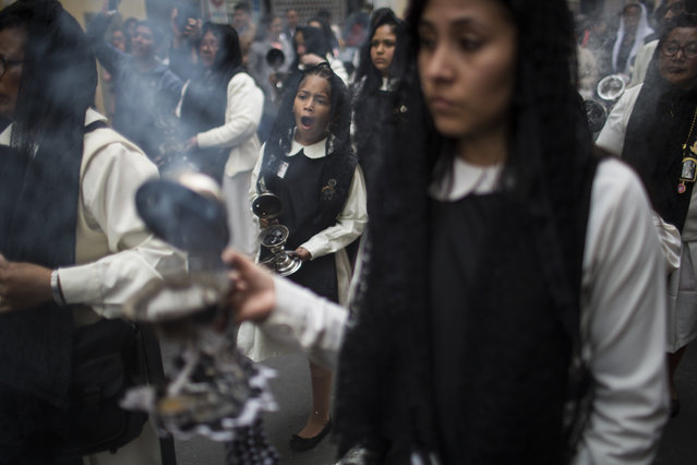 In this August 30, 2017 photo, a girl yawns during a procession celebrating the feast day of Santa Rosa de Lima, Peru's patron saint, in downtown Lima, Peru. Santa Rosa de Lima was the first person born in the Americas to be canonized by the Catholic church. She is also the co-patroness of the Philippines, but remains the primary patroness of Peru and Latin America's indigenous. (Photo by Rodrigo Abd/AP Photo)
