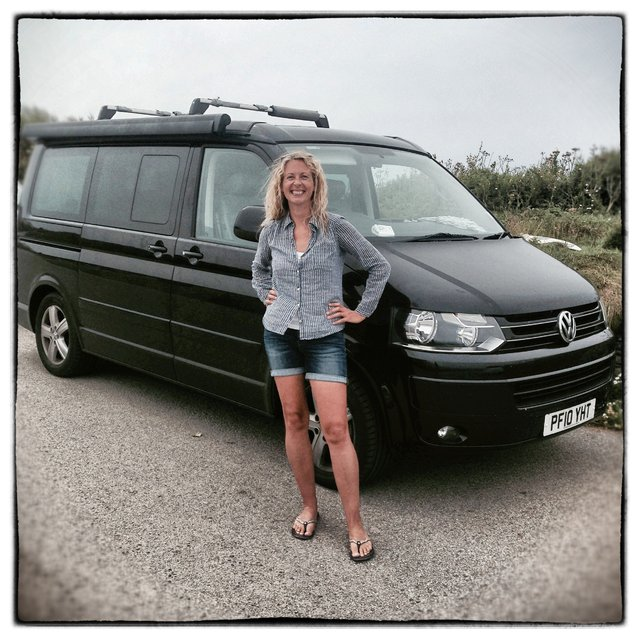 Sally Lawton from Croyde in Devon poses for a photograph besides her 2010 fifth generation T5, Volkswagen Transporter California in Newquay on August 8, 2014 in Cornwall, England. The van, which she bought four years ago is one of a number she has owned. (Photo by Matt Cardy/Getty Images)