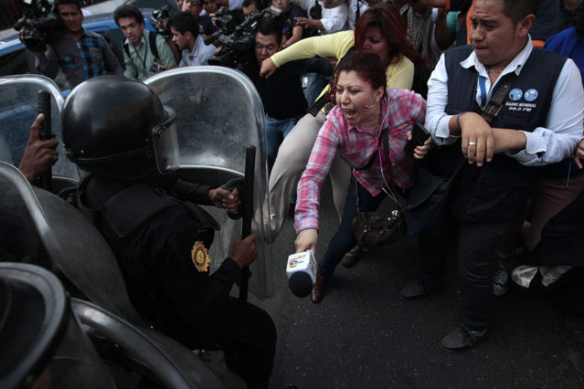 Guatemalan journalists clash with members of the Penitentiary System police as they try to cover the hearing of former Guatemalan vice President Roxana Baldetti, outside the court of justice in Guatemala City, Guatemala, 25 August 2015. Former Guatemalan vice-president Roxana Baldetti refused to testify during a court hearing in which prosecutors accused her of leading a network of customs corruption, a case in which President Otto Perez Molina is also implicated. (Photo by Esteban Biba/EPA)