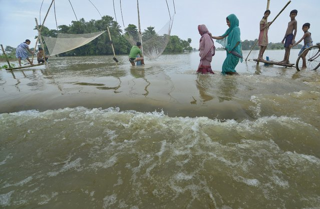 Picture made available on 18 August 2014 showing villagers crossing flood waters in the flood affected Morigaon district of Assam state, India, 17 August 2014. (Photo by EPA/STR)