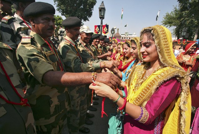 "Indian women tie ""Rakhis"" or traditional Indian sacred threads onto the wrists of Indian Border Security Force (BSF) soldiers during the Raksha Bandhan celebrations at the India-Pakistan joint check post at the Wagah border on the outskirts of Amritsar, India, August 29, 2015. (Photo by Munish Sharma/Reuters)"