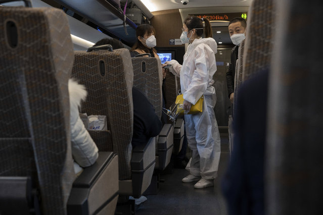 A traveler wearing a protective suit chats with another onboard a train leaving from the train station in Beijing on Sunday, March 29, 2020. As the coronavirus epicenter has shifted westward, the situation has calmed in China, with falling death rates and most new cases coming from abroad, restrictions on travel have been slowly lifted. (Photo by Ng Han Guan/AP Photo)